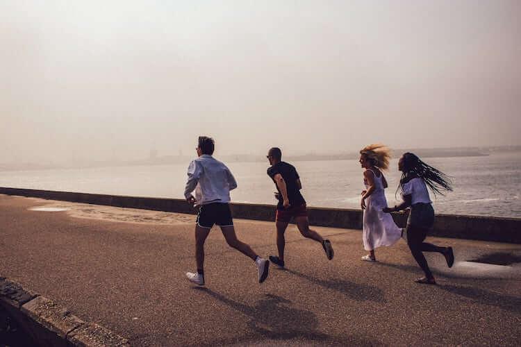 Vier junge Menschen rennen am Strand entlang